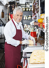 Happy Salesman Wrapping Cheese At Counter In Shop - Portrait...