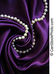 White pearls on a lilac silk as background
