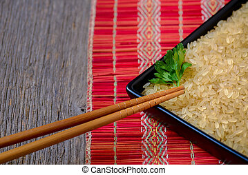 Rice with wooden chopsticks in a black ceramic vessel - rustic view.