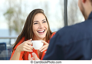 Happy woman dating in a coffee shop looking at her partner...