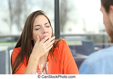 Woman bored in a bad date - Woman bored or tired yawing in a...