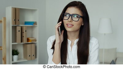 Pretty brunette businesswoman with glasses sitting at desk talking on the phone in office