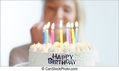 Happy Woman Blowing Out Candles on Birthday Cake - Closeup...