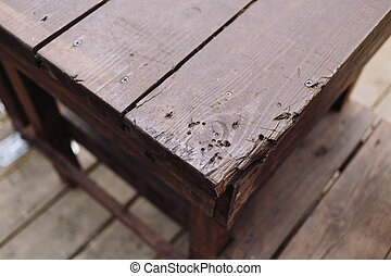 Corner of brown wooden table. Outdoors photo.