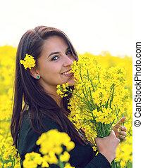 Beautiful Woman holding a bunch of rape flowers Rape Field...