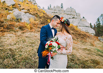 Handsome groom in stylish blue suit embracing white dressed bride holding bouquet of roses on idyllic pastoral landscape with rocks and fence as backround