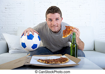 man in stress watching football game on television eating...