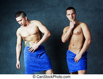 sexy men - two attractive young men with towels on their...