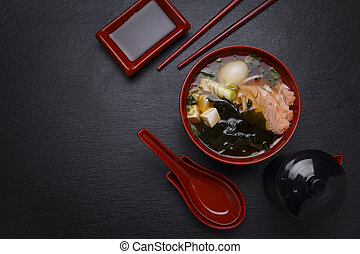 Japanese miso soup in a red bowl on the table