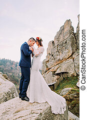 Handsome groom in stylish blue suit lovingly kissing his white dressed bride hands on majestic mountain landscape with big rocks as backround