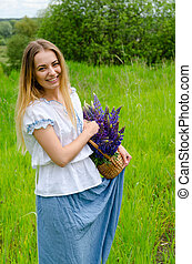 Beautiful girl with basket of wild flowers in hands
