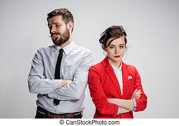 The sad business man and woman conflicting on a gray...