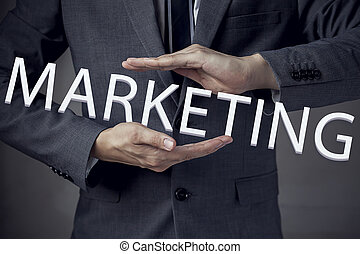 """Businessman in suit with two hands in position to protect the word """"MARKETING"""" (focus on hand, blur out the suit)."""