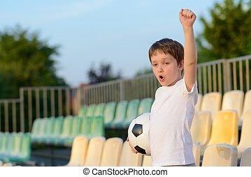 Little boy - football team fan - supporter on the stadium