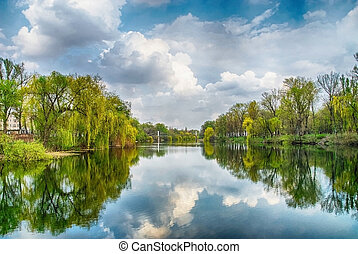 River in park under blue sky and white clouds