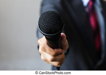 Man in business suit holding a microphone conducting a...