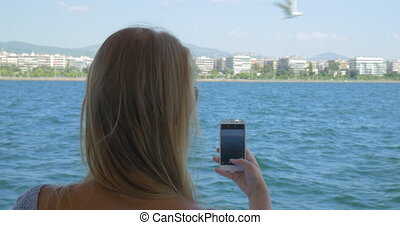 Woman on the ship taking sea pictures on mobile