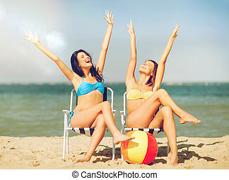 girls sunbathing on the beach chairs - summer holidays and...