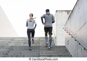 couple running upstairs on city stairs - fitness, sport,...