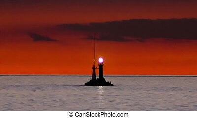 Lighthouse warning at sundown - Small lighthouse silhouette...