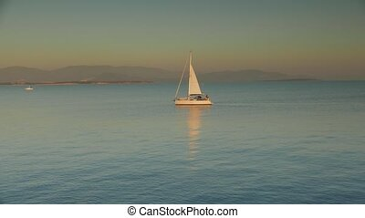 Sailing yacht with white sails into the sunset. 4k
