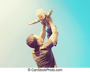 Happy father and son playing having fun together outdoors...