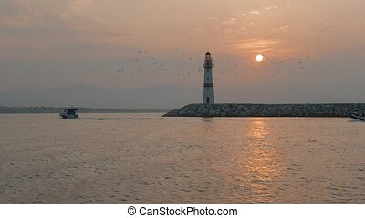 Boats passing lighthouse with rising sun at background. 4K.