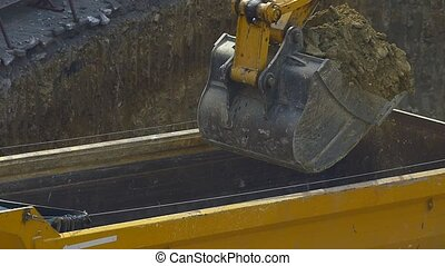 Dump truck being loaded with soil by shovel slow motion....