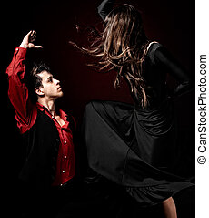 Young couple passion flamenco dancing on red light...