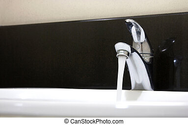 Open faucet and water flow in a bathroom
