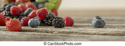Mixed berry fruits scattered on a wooden desk - Panoramic...