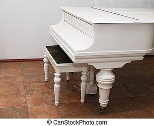 white grand piano and bench in a room