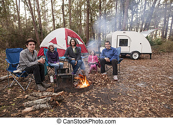 Family of five camping in the woods with campfire, tent, and...