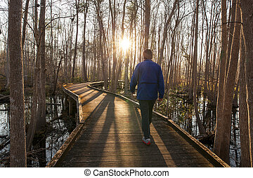 Man walking trail in early morning