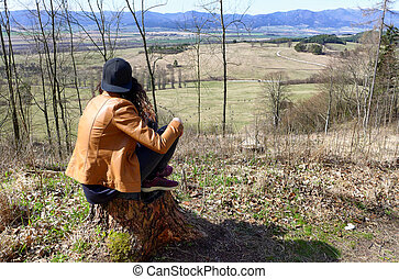 Lonely girl in forest on tree