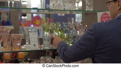 Man taking a shot of glass in the store - Young man looking...