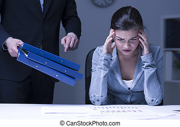 Victim of an evil boss - Tired and overworked woman working...