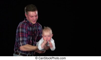 Affectionate father playing with baby son at home - lifting...