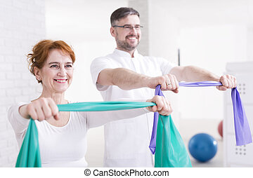 Training together is more fun - Happy aged woman exercising...