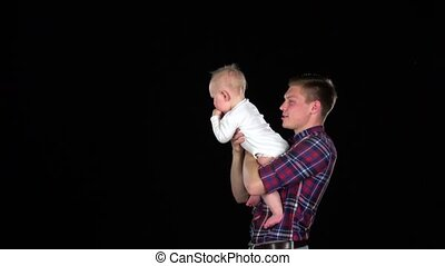 Dad tosses baby into the air. Black - Father and baby...