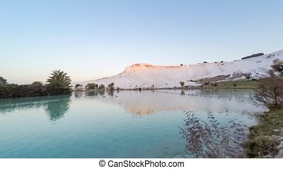 Sunrise in Pamukkale (Turkey) with the white hill and its reflection in the natural pool. Timelapse, 4k
