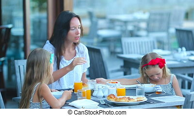 Young mother and adorable little girls having breakfast at...