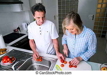 Senior man and woman preparing breakfast Sunny morning...