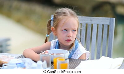 Adorable little girl having breakfast at outdoor cafe