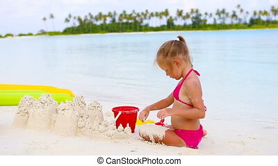 Little girl playing with beach toys during tropical vacation...