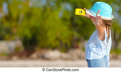 Adorable little girl making selfie in at tropical beach