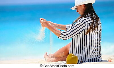 Young beautiful woman on white beach with coconut