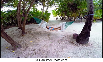 Adorable little girl relaxing in hammock on beach - Adorable...