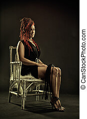Mistress with lash sitting on a chair