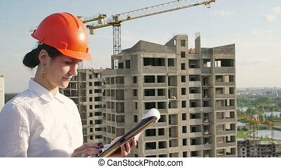 Architect looking on project on construction site - woman...